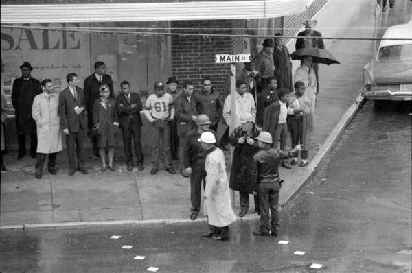 Freedom Day, January 22, 1964, Hattiesburg, Miss., in front of the Sears Roebuck. Participants include: Howard Zinn, third from left; John Lewis, arms crossed, sixth from left; Bob Moses, immediate left of street sign; and James Forman, immediate right of street sign. Image: Winfred Harmon Moncrief.